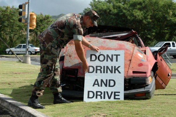 "A uniformed soldier posting a ""Don't Drink and Drive"" poster on the front of a mangled sports car."